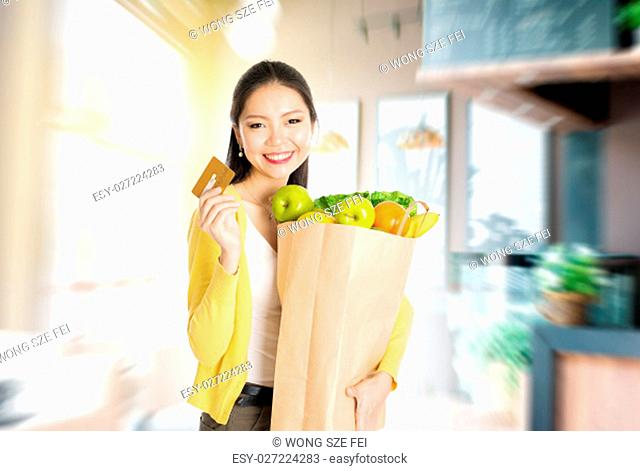 Young Asian woman hand holding shopping paper bag filled with fruits and vegetables and credit card in market store or cafe
