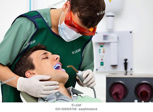 Dentist using UV light on patients teeth
