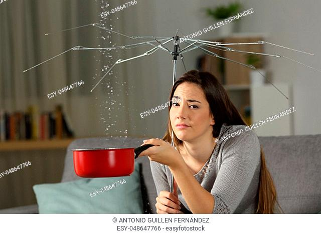 Sad homeowner with water leaks and a broken umbrella sitting on a couch in the living room at home. Bad insurance concept