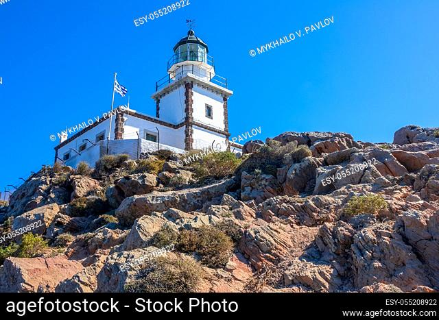 Greece. Rocky mountain on a sunny day. Lighthouse building against the blue sky and national flag