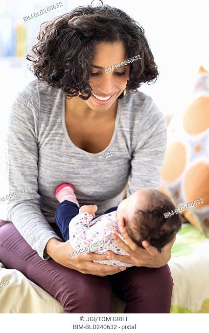 Hispanic mother cradling baby daughter