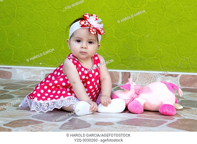 little girl in a red and white polka-dot dress posing for the camera