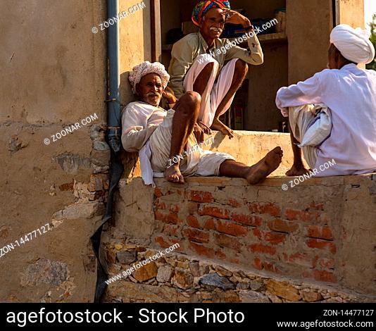 PUSHKAR, INDIA - NOVEMBER 19, 2012: Indian men sit on the road near houses in the city of Pushkar
