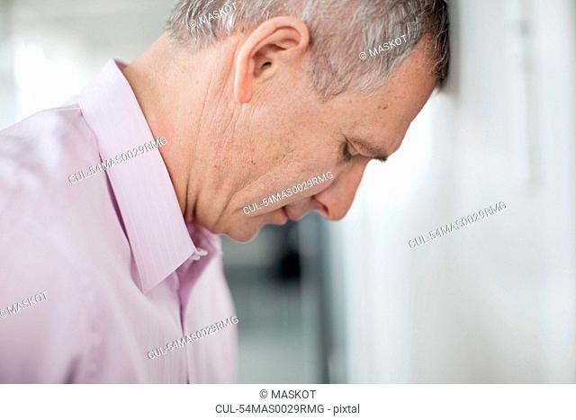 Businessman leaning forehead on wall