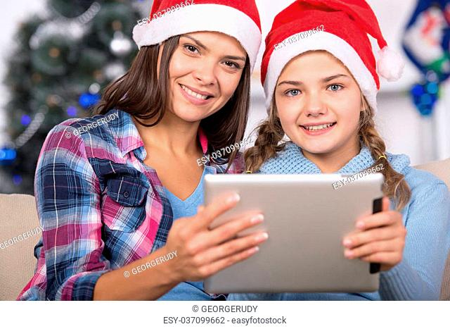 Beautiful young woman and her daughter with the tablet at Christmas time are looking at camera
