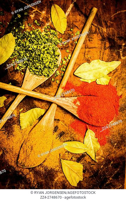 Top kitchen view of curry spice, red pepper and chopped herbs on wooden spoons. Eastern style cooking