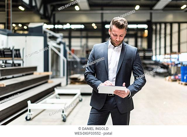 Businessman with tablet standing on factory shop floor