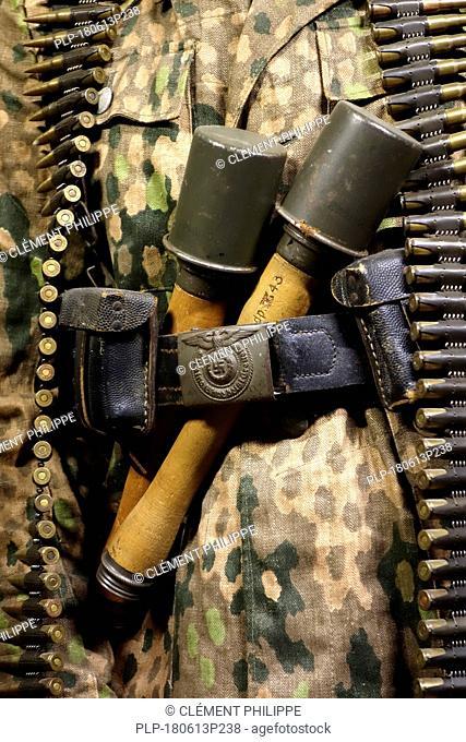 Close up of two WW2 stielhandgranaten tucked under pants belt of German SS soldier carrying machine gun ammunition belt