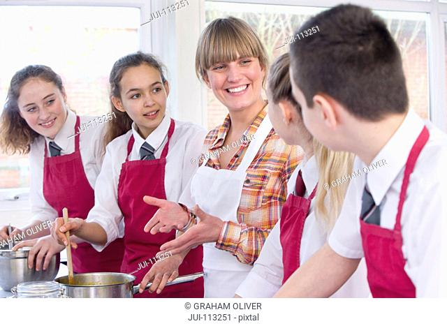 Smiling teacher guiding high school students cooking in home economics class