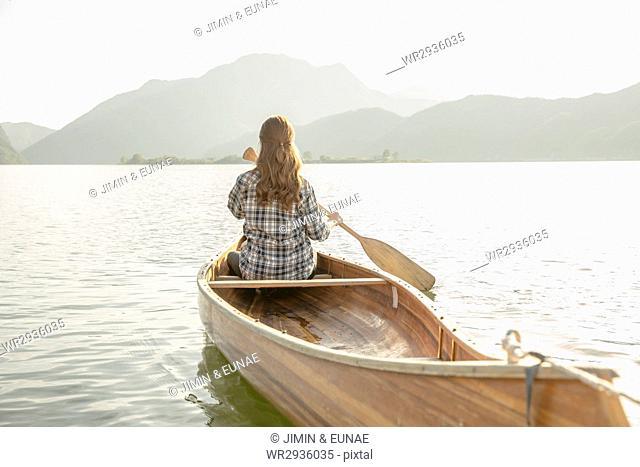 Back of your female traveler paddling a canoe