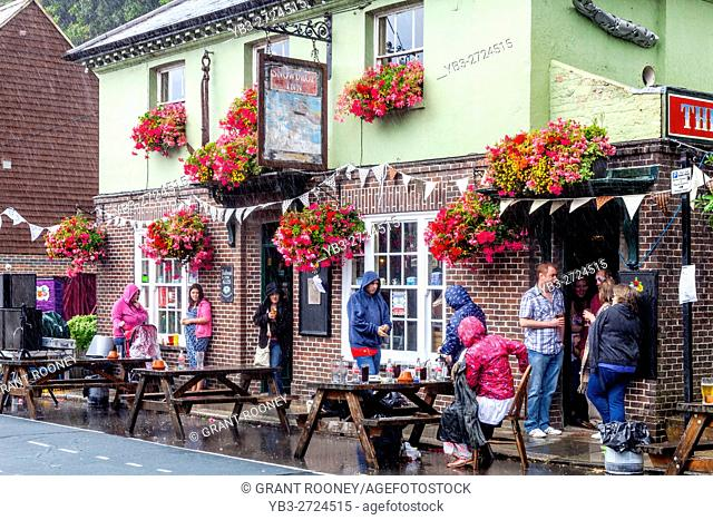 People Shelter From The Rain Outside The Snowdrop Pub In The Market Town Of Lewes, East Sussex, UK