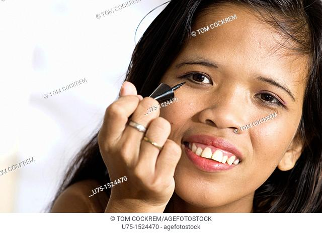 Asian model applying eyebrow pencil in studio setting