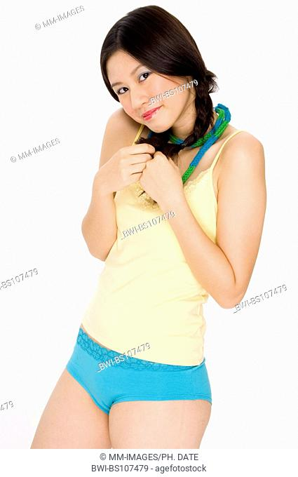 pretty young Asian teenage girl in colorful underwear, coquettish playing with her plaits