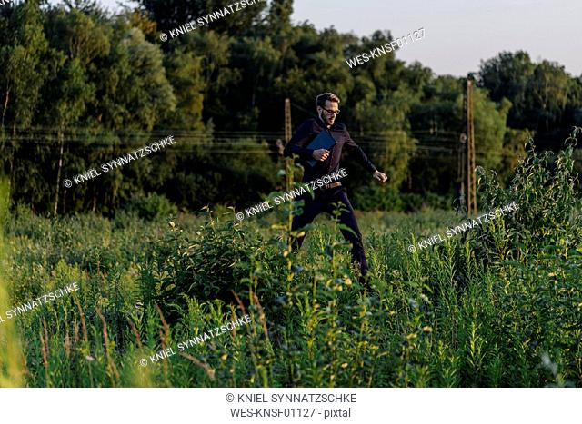 Businessman running with laptop in the nature