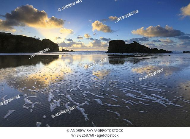 Sunset reflected in wet sand on the beach at Perranporth on the North Coast of Cornwall, the image was captured in mid February