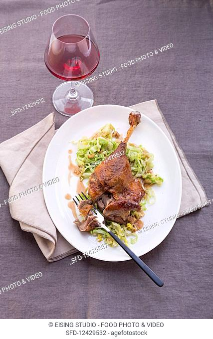 A goose leg with spicy cabbage served with red wine