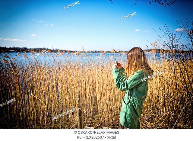Young teenage girl Smartphone taking photo lake