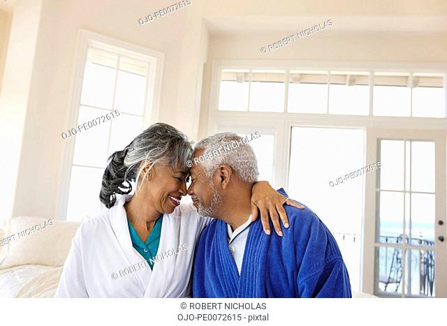 Smiling senior couple in bathrobes hugging face to face in bedroom