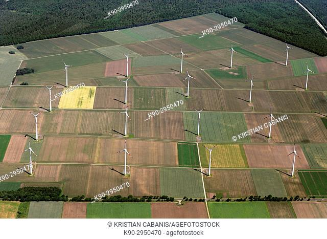 Aerial view of a windfarm and wind turbines in the middle of agricultural farmland with green fields, forest and a highway passing, Lower Saxonia, Germany