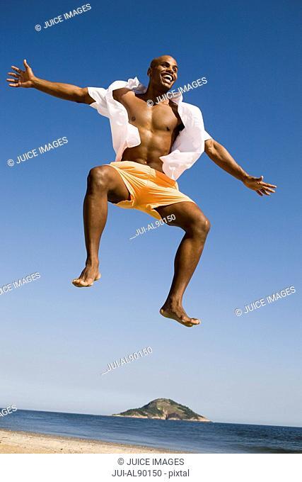 African man jumping at beach