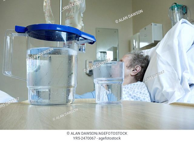 Elderly lady in her nineties in bed on NHS hospital ward with jug of water on bedside table. England, United Kingdom