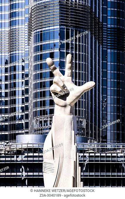 Statue in front of the Burj Khalifa in Dubai, the highest building of the world, during golden hour. This hand sign was coined as a logo for the UAE by Sheikh...
