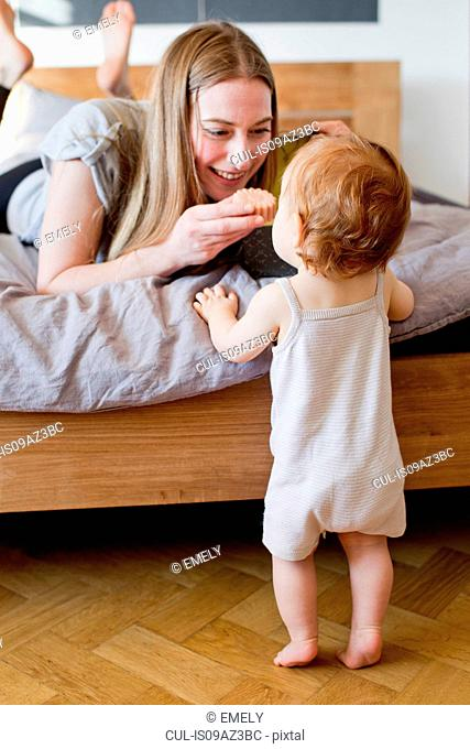 Mid adult woman feeding baby daughter a biscuit from bed