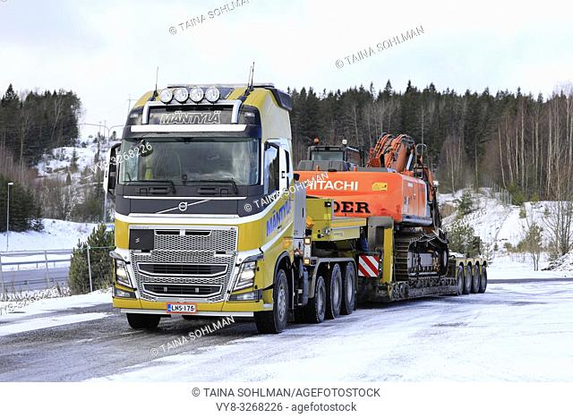 Salo, Finland - March 9, 2019: Volvo FH16 truck Mantyla with low loader trailer carrying Hitachi ZX 350LC excavator as wide load on a day of winter