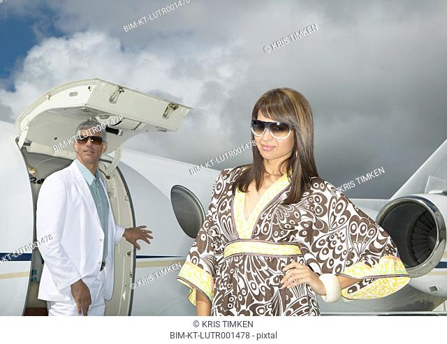 Couple standing in front of small jet, Nobato, California, United States
