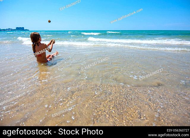 Girl sitting on the seashore and throws sand balls