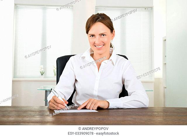 Happy Businesswoman With Pen Signing Cheque At Desk