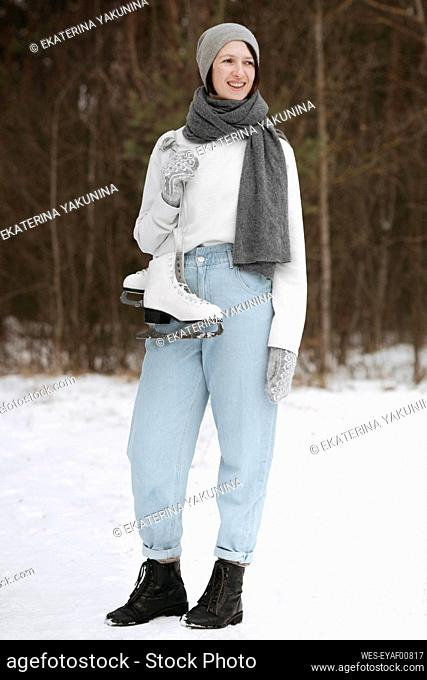 Portrait of smiling woman with ice skates in winter