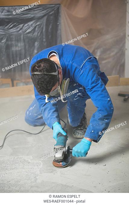 Worker smoothening cement with an angle grinder