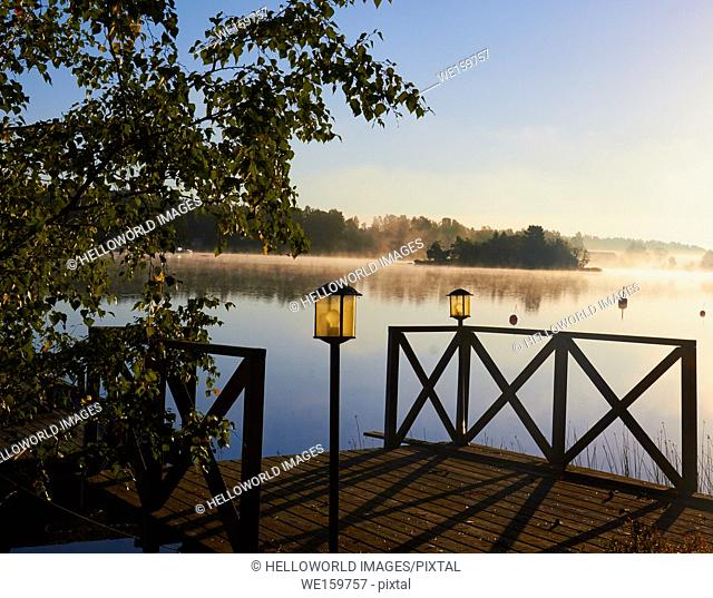 Wooden lakeside platform on misty summer morning, Ljustero, Stockholm County, Sweden, Scandinavia. . Ljustero is an island in the northern part of the Stockholm...