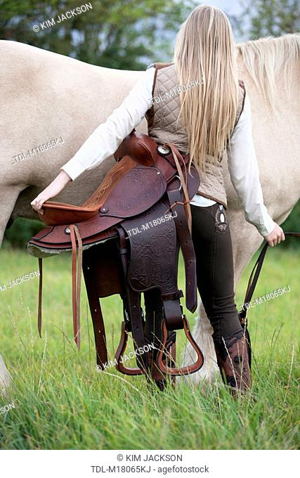 A young woman holding a western saddle