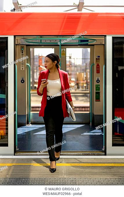 Businesswoman with cell phone getting out off the train, London, UK
