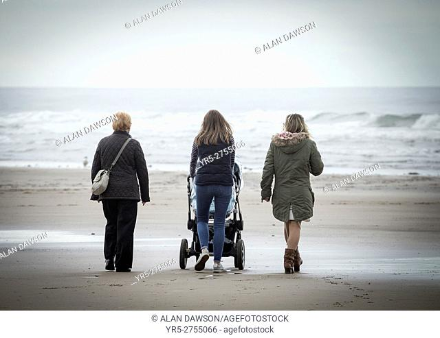 Woman walking on beach with baby in pushchair on a cold and grey day at Saltburn by the Sea, North Yorkshire, England. United Kingdom