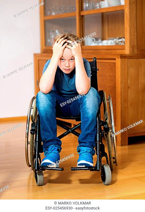 disabled boy in wheelchair at home is sad