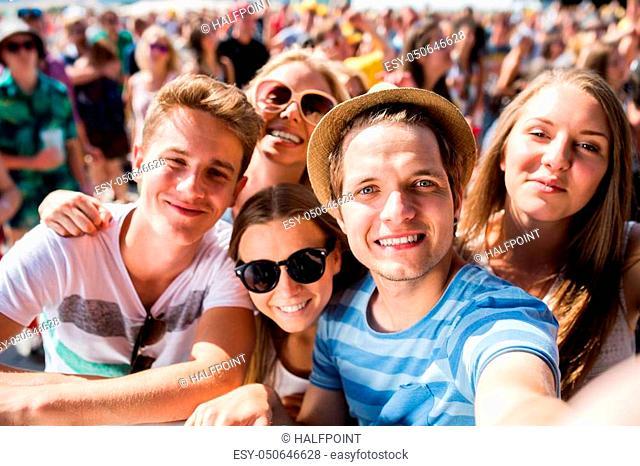 Teenagers at summer music festival in crowd taking selfie, enjoying themselves