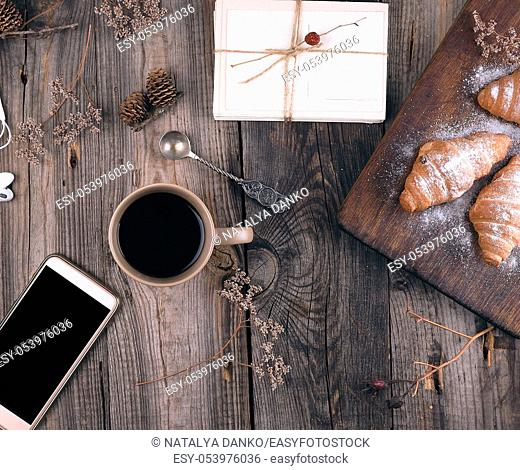 smartphone with blank black screen, brown ceramic cup with coffee and baked croissants sprinkled with icing sugar on gray wooden background, top view