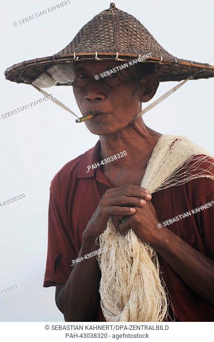 A man carries a fishing net while smoking at Ngapali Beach, Myanmar, 10 April 2013. Photo: Sebastian Kahnert   usage worldwide. - Amarapura/Birma