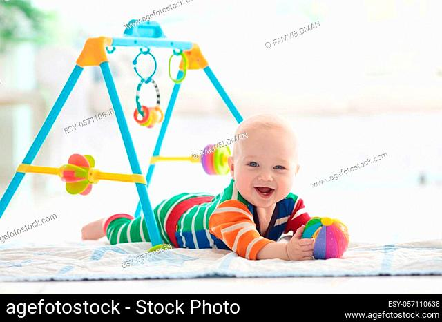 Cute baby boy on colorful playmat and gym, playing with hanging rattle toys. Kids activity and play center for early infant development