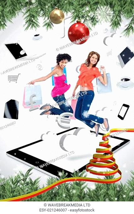 Composite image of two smiling women jumping on a tablet pc
