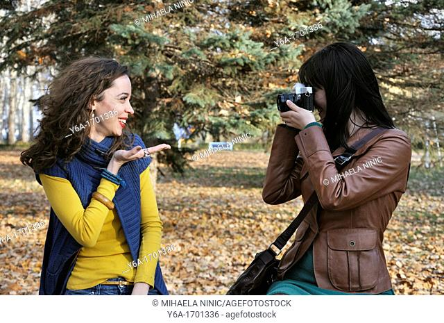 Young woman photographing her friend in park