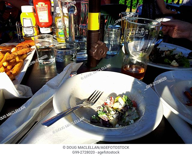 A half full bowl of salad placed on a table with condiments, glasses, deep fried chicken taken late in the afternoon on the porch of an old inn restaurant