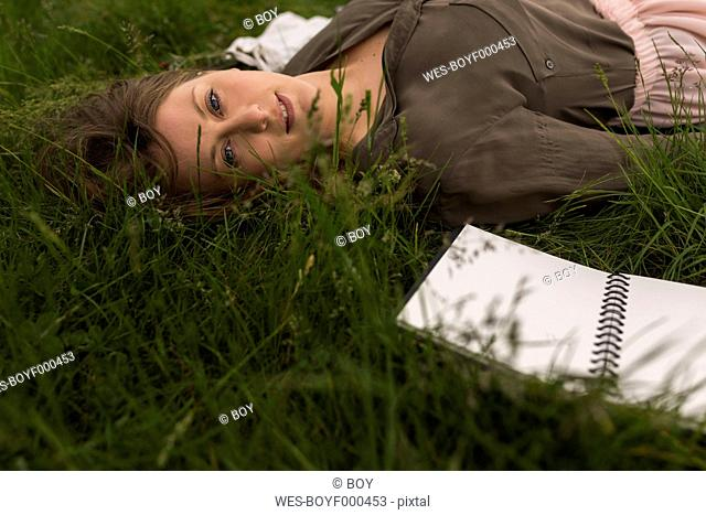 Portrait of daydreaming woman lying on a meadow
