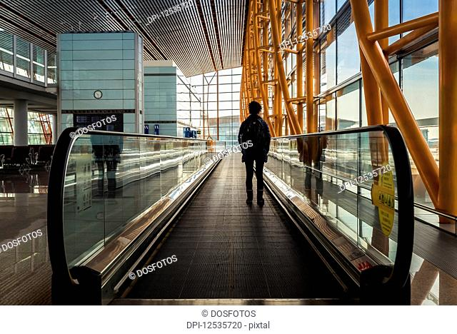 Passenger standing on moving sidewalk in airport terminal building, Beijing Capital International Airport; Beijing, China