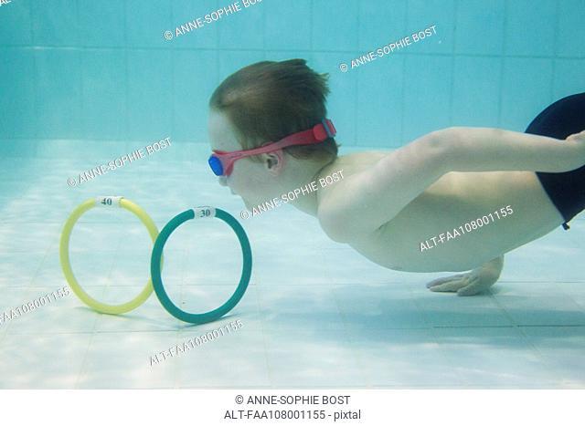 Boy retrieving rings from bottom of swimming pool