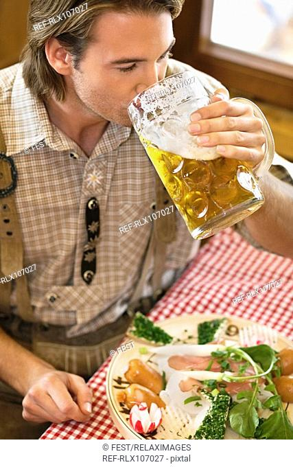 Close-up of young man drinking beer at Oktoberfest, Munich, Germany