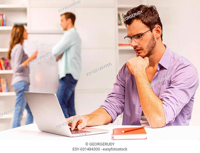 Young attractive businessman in casual clothes and eyeglasses using laptop while working in office, in the background man and woman talking